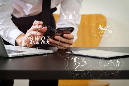 SWOT Analysis virtual diagram with Strengths, weaknesses, threats and opportunities of company.businessman working with smart phone and digital tablet and laptop computer on wooden desk in modern office Archivio Fotografico