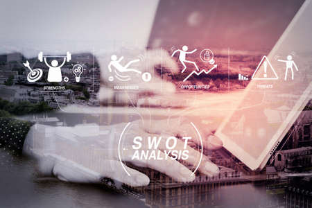 SWOT Analysis virtual diagram with Strengths, weaknesses, threats and opportunities of company.businessman hand working with laptop and digital docking keyboard tablet computer in modern office with London city. Stock Photo