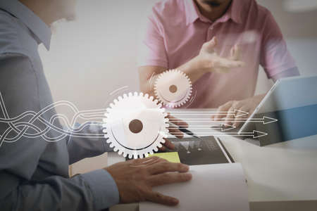 Thinking about structuring virtual diagram of business process with solutions. Businessmen working together on a document and using smart phone and digital tablet and laptop computer in modern office