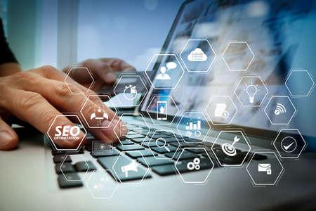 SEO-Optimierung für Website mit mobiler Website und virtuellem Landingpage-Diagramm. Hände mit Laptop und Kreditkarte als Online-Shopping-Konzept