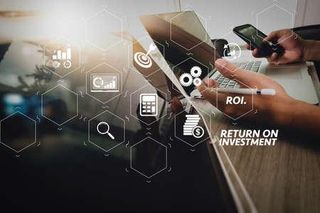 ROI Return on Investment-Indikator im virtuellen Dashboard zur Verbesserung des Geschäfts. Designerhand, die mit digitalem Tablet und Laptop-Computer und Buchstapel und Augenglas auf Holzschreibtisch als Konzept arbeitet