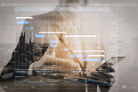 Project manager working and update tasks with milestones progress planning and Gantt chart scheduling virtual diagram.Double exposure of success businessman open his hand with London building,city. Stock Photo