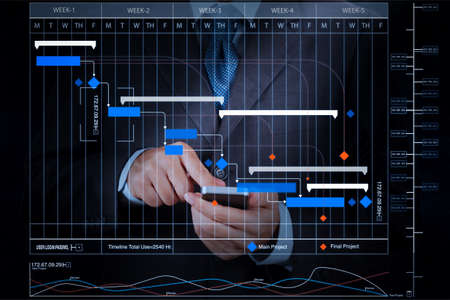 Project manager working and update tasks with milestones progress planning and Gantt chart scheduling virtual diagram.businessman hand using mobile smart phone. Stock Photo
