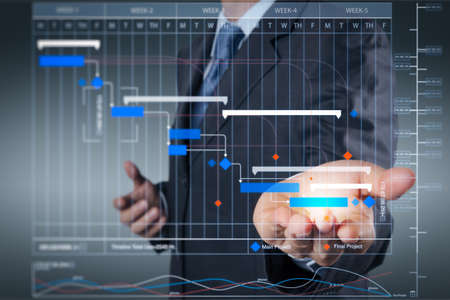 Project manager working and update tasks with milestones progress planning and Gantt chart scheduling virtual diagram.business man with an open hand as showing something concept. Stock Photo