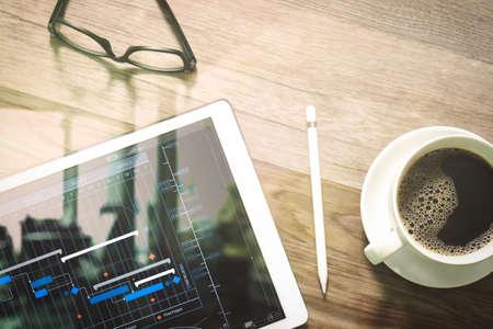 Gerente de proyecto que trabaja y actualiza tareas con planificación de progreso de hitos y diagrama virtual de programación de diagrama de Gantt.Taza de café y teclado inteligente de base de mesa digital, anteojos, lápiz óptico en la mesa de madera. Foto de archivo