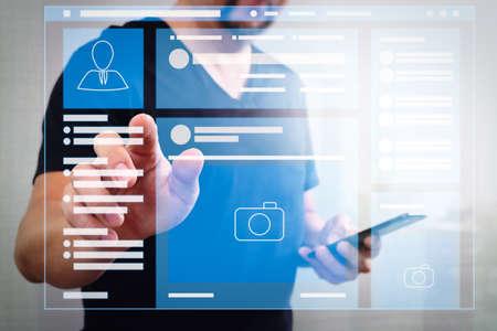 Navigateur de page Web de l'interface VR de page de médias sociaux sur l'ordinateur portable. Main d'homme d'affaires appuyant sur un bouton imaginaire, tenant un téléphone intelligent, icônes virtuelles graphiques d'écran numérique