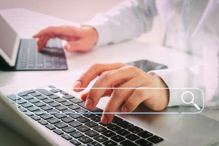Concepto de red de información de datos de navegación de búsqueda con barra de búsqueda en blanco. Cerca del empresario escribiendo tableta digital con teclado y computadora portátil en el escritorio blanco en la oficina moderna