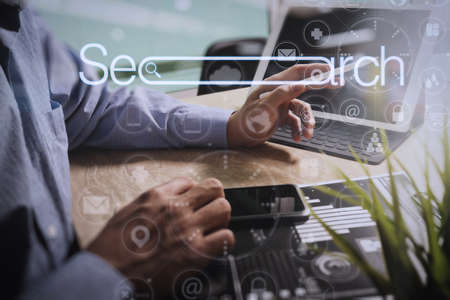 Searching Browsing Internet Data Information Networking Concept with blank search bar.Designer Businessman hand using smart phone,mobile payments online shopping with digital tablet docking keyboard computer.