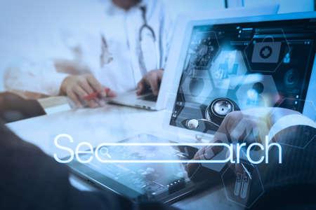 Ricerca esplorando il concetto di rete di informazioni sui dati di Internet con barra di ricerca vuota. Mano di medico medico lavorando con smart phone, computer tablet digitale, occhiali stetoscopio sulla scrivania in legno.