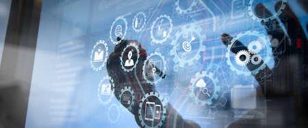 E-Learning mit verbundenen Zahnrädern verbundenes Diagramm virtuelles Armaturenbrett. Geschäftsmannhand, die an Laptop-Computer mit Geschäftsstrategie der digitalen Schicht und Diagramm der sozialen Medien auf Holzschreibtisch arbeitet