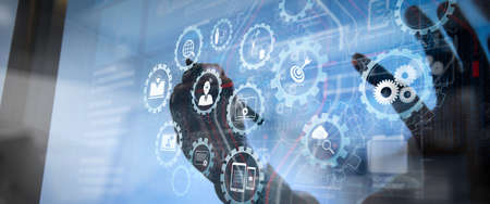E-learning with connected gear cogs connected diagram virtual dashboard.business man hand working on laptop computer with digital layer business strategy and social media diagram on wooden desk Stock Photo
