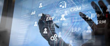 Arquitectura del sistema ERP (Enterprise Resource Planning) con conexiones entre inteligencia empresarial (BI), producción, módulos CRM y diagrama de RRHH. Mano de empresario mediante teléfono inteligente, pagos móviles online. Foto de archivo