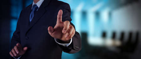 businessman workimg on VR blank wide touch screen computer on office blur background.