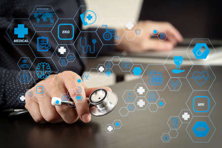 Health care and medical technology services concept with flat line AR interface.smart medical doctor working with stethoscope and laptop computer on dark wooden desk