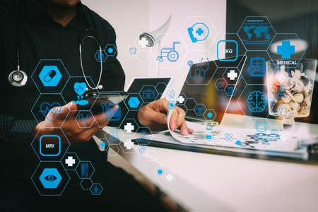 スマートメディカルドクターは、現代オフィスのウッドデスクで、スマートな電話とデジタルタブレットとラップトップコンピュータと聴診器を扱うフラットラインARインタフェースと医療技術サービスのコンセプト 写真素材 - 107981124
