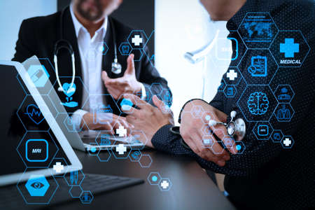Health care and medical technology services concept with flat line AR interface.Medical co working concept,Doctor working with digital tablet and laptop computer formeeting his team in modern office 写真素材