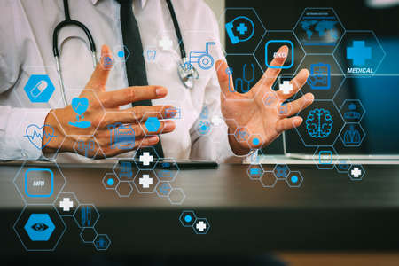 Health care and medical technology services concept with flat line AR interface.smart medical doctor working with smart phone and digital tablet computer and stethoscope on wood desk in modern office 写真素材