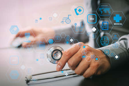 Health care and medical technology services concept with flat line AR interface.smart medical doctor working with stethoscope and mobile phone on dark wooden desk in modern hospital 写真素材