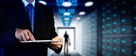 Businessman working with VR wide blank screen computer on server room in background. Stock Photo
