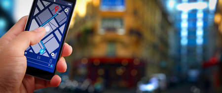 Close up of Tourist using GPS map navigation on smartphone application screen for direction to destination address in the city with travel and technology concept.