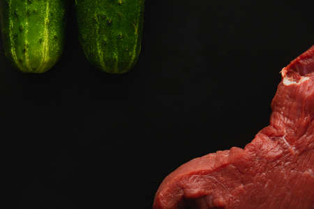 Fresh raw beef steak, meat with two green cucumbers on a black background, close up, copy space.