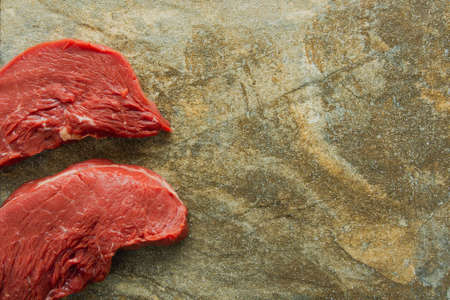 Fresh raw beef steak, meat against a granite stone background, close-up, copy space. 版權商用圖片