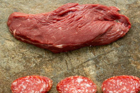 Fresh raw beef steak, meat and slices of sliced sausage on a background of granite stone, close-up. 版權商用圖片