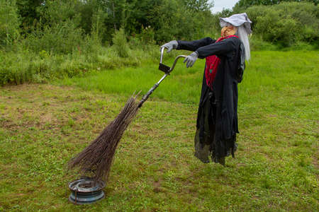 A mannequin of a witch's grandmother on a broom at the wheel of a Bicycle in a summer forest.