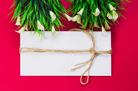 White envelope, envelope wrapped with rope, red background with a white flower and green leaves.