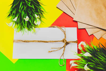 White envelope, envelope wrapped with rope, multicolored background with a white flower and green leaves.