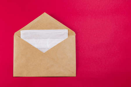 Medical face mask in a gray envelope on a red background, close-up.