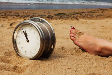 Old round ship clock on the sand and the foot of a sunbathing girl on the beach, summer by the sea, the background of the wave.