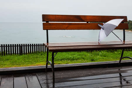 White and gray children's umbrella on a rainy summer day on a wooden bench against the sea, summer holidays.