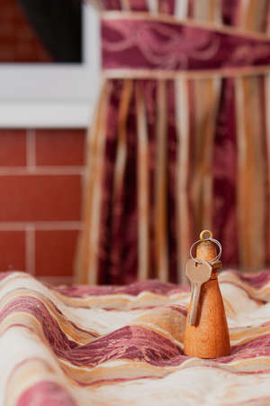A key on a wooden key chain from a hotel room on a blanket on the bed against the background of a window curtain. Banque d'images