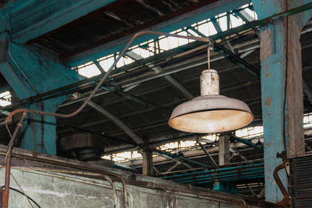 An old lamp in the shop of an abandoned factory.