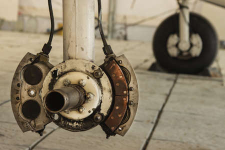 Landing gear of a small private plane standing in the hangar, replacement of the plane's brake pads, wheel hub.