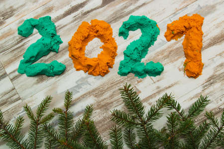 Bright colored sand clay 2021 figures on a gray stripe background with branches of a Christmas tree.