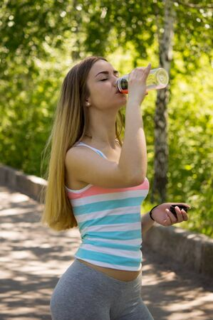 isotonic: portrait of young sporty woman drinking isotonic drink at park. Woman in a  striped shirt in the summer morning Stock Photo