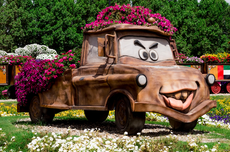 DUBAI, UAE - APRIL 23,2015. Park alley with many flowers with close up detail of an brown cartoon  car covered in blooming pink flowers and greenery. Dubai Miracle Garden, UAE. United Arab Emirates