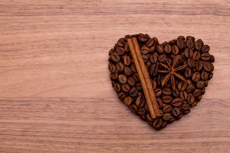 Handmade heart made of coffee beans. Cinnamon stick and star anise on it.