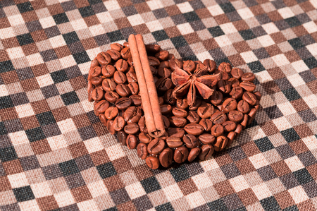 Handmade heart made of coffee beans on checked napkin. Cinnamon stick and star anise.