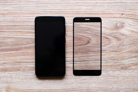 black phone and the protective glass on wooden background