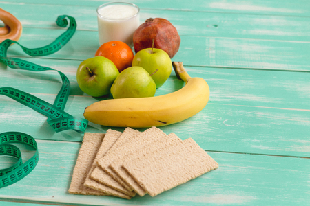 fruit with Cup of yogurt and bread separated by a measuring tape with chocolate and donuts on a green wooden background, concept of proper nutrition