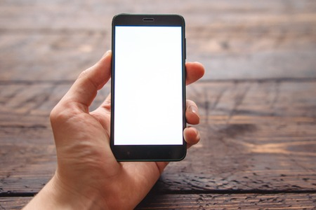mens hand holding smartphone with blank screen for your logo or design on dark wooden table Stockfoto