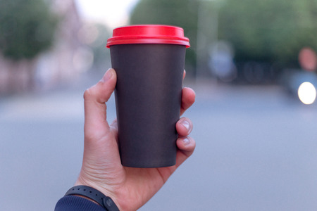 Close-up of male hand holding coffee with space for your text or logo