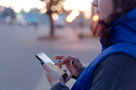 young woman walking in the night city streets using modern smartpone  with blank screen with copy space for your text or logo, mock up of modern smartphone device