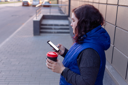 close-up of female hands holding coffee and smartphone with blank screen for your logo or text message, girl walking around town at night and drinking cappuccino