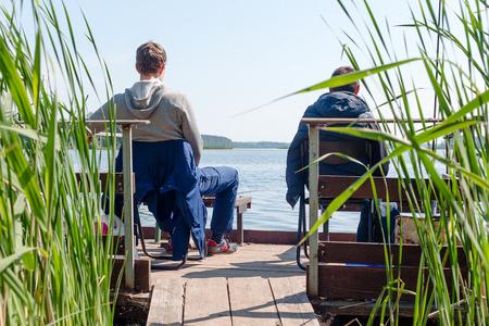 two men fishing on the pier bridge