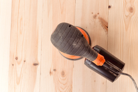 top view of the orbital sander on a wooden table