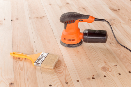 closeup of the orbital sander and paintbrush  on a wooden table